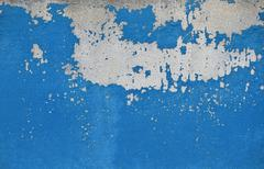 Flakes of old blue paint on grey concrete wall - stock photo