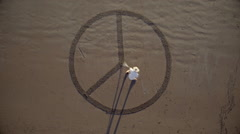 Man drawing the peace symbol in the sand Stock Footage