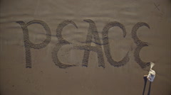 Man writing a the word peace in the sand - stock footage