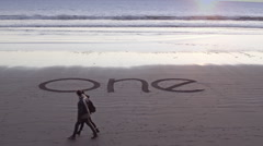 The word one writing in the sand during sunset - stock footage