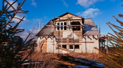 Destroyed wooden house against the sky - stock footage