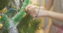 Girl is Decorating New-Year Tree With Blue Beads Garlands Putting a Garland to Stock Footage