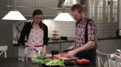 Man and woman cut vegetables on wooden boards Stock Footage