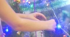 Girl is Putting a Toy Snowman to Pine Decorated New-Year Tree Bell-Garlands and Stock Footage