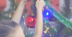 Girl is Putting a Red Christmas Ball Decorated New-Year Tree Pine Bell-Garlands Stock Footage
