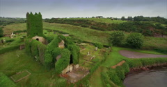 Aerial drone view of flying over Irish Estuary to an abandoned church covered in - stock footage