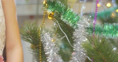 Girl in Crown And Earrings is Trying to Put a Toy to a New-Year Tree Pine Stock Footage