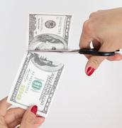 100 dollar cut with scissors on white - stock photo