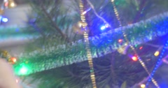 Girl in Violet Earrings is Putting a Blue Beads Garland to a New-Year Tree Pine Stock Footage
