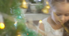 Girl is Walking Around a Pine New-Year Tree Talking Shying Golden Bell-Garland Stock Footage