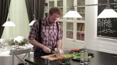 Man cut green onions on a wooden board Stock Footage