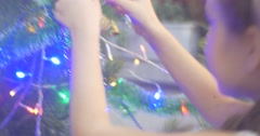 Girl is Putting a Golden Cone to Decorated New-Year Tree Pine Garlands and Stock Footage