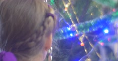 Girl is Walking Around a New-Year Tree Pine Decorating it With Silver Garland Stock Footage