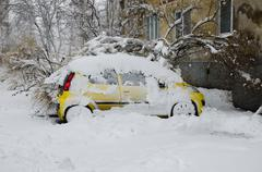 Snow-covered car parked in a snowstorm Stock Photos