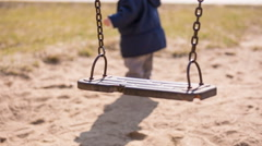 Empty swing swaying at playground with toddler on background Stock Footage