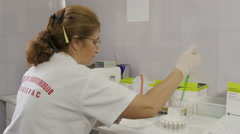 Female lab technician performing blood test, puts blood in device for analysis. Stock Footage