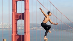 Ballet Dancer balancing on a pole at the Golden Gate Bridge Stock Footage