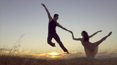 Female ballet dancer posing and male ballet dancer jumping in the air in slow Stock Footage