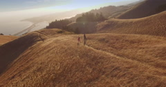 Aerial Drone view of male and female ballet dancers on a dry grass ridge on a Stock Footage