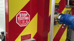 Warning sign to STOP TEXTING on mobile phones on the back of a fire truck Stock Footage