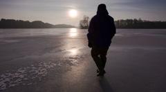 Man walking away on a frozen lake Stock Footage