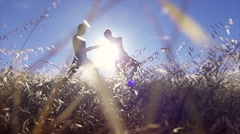 Female ballet dancer posing with male ballet dancer in slow motion in the grass Stock Footage