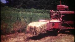3037 farmer bales hay with old equipment - vintage film home movie Stock Footage
