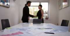 Document and pen on the desk,  business people shaking hands in the background.  Stock Footage