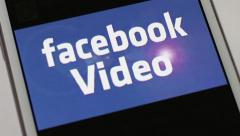 CU smartphone social media - 'Facebook Video' with diagonal dolly out Stock Footage