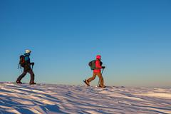 Two skiers walking snowy field - stock photo