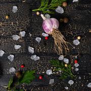 top view of garlic, red, black peppers, sea salt, greenery on cracks black ba - stock photo