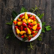 top view of plate with orange, red and yellow hot chili peppers, greenery on  - stock photo