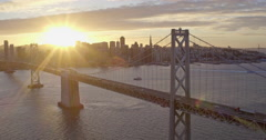 Aerial of Sun Shining through San Francisco Bay Bridge, Golden Hour - stock footage