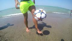 Proffessional football player makes ball tricks bouncing ball on beach sand b Stock Footage