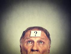 Thinking man with question mark on gray wall background . Stock Photos
