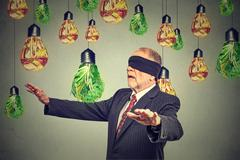 Blindfolded senior man walking through light bulbs shaped as junk food and gr Stock Photos