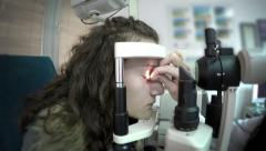 Young girl having her eyes examined by an eye doctor Stock Footage