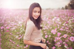 Beautiful asian women smiling in pink cosmos flower field Stock Photos