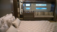 Main cabin with bed in the center and sofa on a luxury yacht  Stock Footage