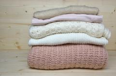 Pile of pink and white woolen sweaters Stock Photos