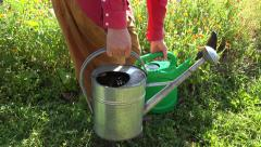 Gardener picking up two full watering cans, 4K Stock Footage