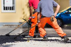 Stock Photo of Asphalt surfacing manual labor.