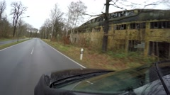 Driving past an old abandoned factory ruin showing partly broken windows 4k Stock Footage