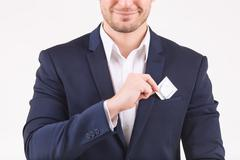 Smiling person putting condom into his breast pocket - stock photo