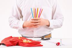 Tailor holding a set of colored pencils - stock photo