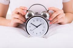 Female hands and alarm clock - stock photo