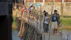 Tourists walking across bamboo bridge,Vang Vieng,Laos Stock Footage