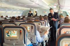 Steward and passengers on commercial airplane. Stock Photos