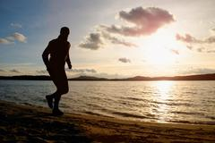 Tall man with sunglasses and dark cap is  running on beach at autumn sunset Stock Photos