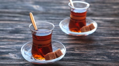 Pouring tea into a cup on a wooden table Stock Footage